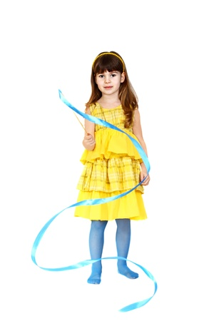 Cute little girl in yellow dress plays with blue ribbon. Portrait isolated on white background