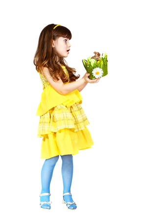 Cute little girl in yellow dress gives an easter bunny. Profile full height portrait isolated on white background