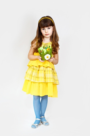 Cute little girl in yellow poses with easter nest in hands. Ful height portrait on natural gray background