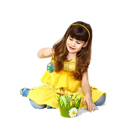 Cute little girl in yellow dress sits and plays with easter egg. Portrait on white background with shadows Stock Photo