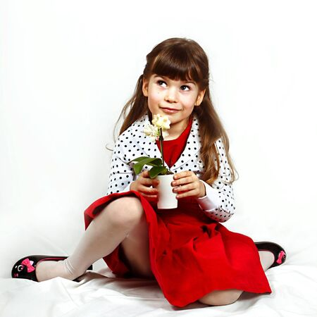 Cute little girl in red dress with orchid in hands sits on crumpled cover. Portrait on white background with shadows