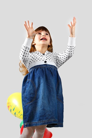 Cute little girl with bad teeth catches balloon. Portrait on gray background Stock Photo