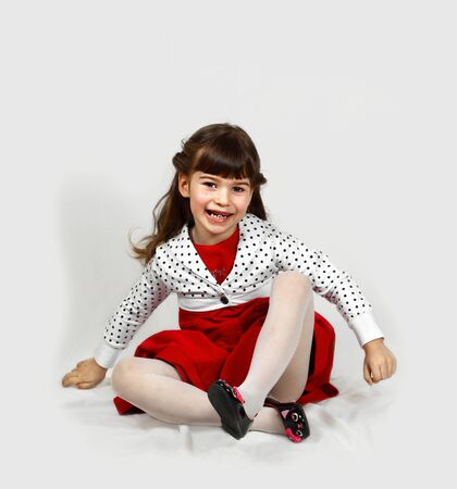 Joyful cute girl in red dress sits on crumpled white coverlet. Portrait on light gray background with soft shadows