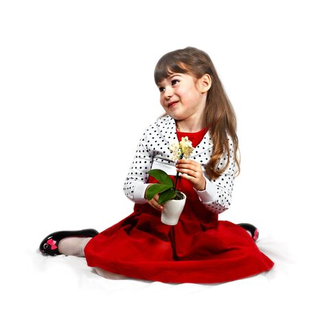 Flirtatious cute girl with orchid in hands dressed in red sits on folded cover. Portrait on white bacground with light shadows