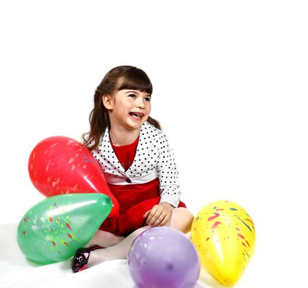 Happy little girl sits among multicolored balloons. Portrait on white background with shadows Stock Photo