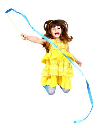 Little girl in yellow dress jumps with blue ribbon in hand. Isolated on white background
