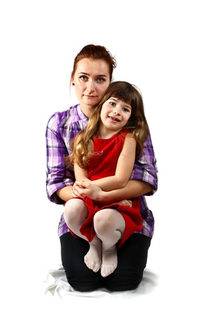 Kneeling mother holds her daughter in arms. Portrait on white background
