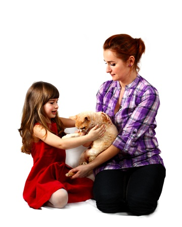 Mother and young daughter play with red cat. Portrait on white background with shadows