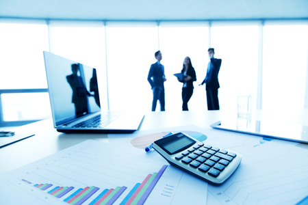 desk with laptop and finance report with business people in background Stock Photo