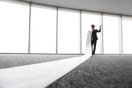 white sheet: businessman reading long white sheet