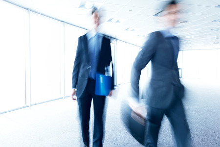 business men walking through office blurred