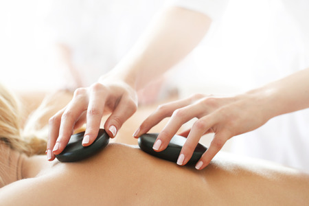 stone therapy: woman having stone therapy at spa session Stock Photo