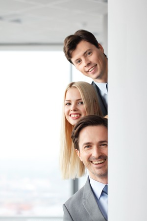 looking in corner: Happy business people looking out from corner in office Stock Photo