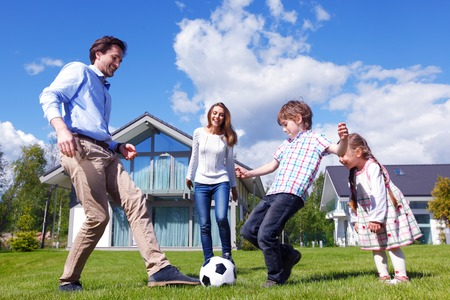 family on grass: family playing football in front of their house Stock Photo
