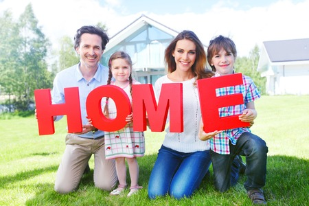 happy holding home letters in front of their house