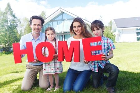 幸せな家の前でホームの文字を保持しています。 写真素材 - 41500680