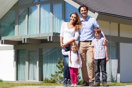 gelukkige familie die zich in de voorkant van het huis Stockfoto