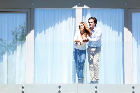 若いカップルの家のバルコニーの上に立って