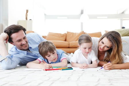 happy family drawing pictures with coloring pencils