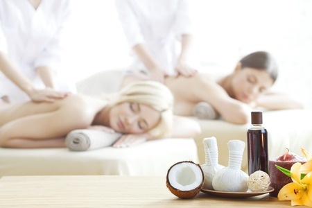massage herbal: Spa massage tools and women getting massage on background