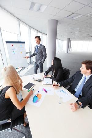 I lavoratori di incontro di lavoro in cerca di presentazione dei documenti contabili in ufficio moderno