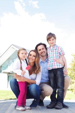 家の前に立って幸せ家族います。