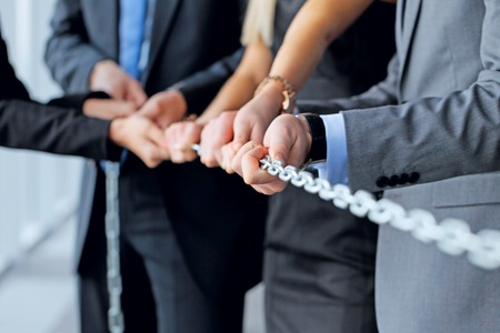 Businessmen pulling chain, teamwork togetherness concept Stock Photo