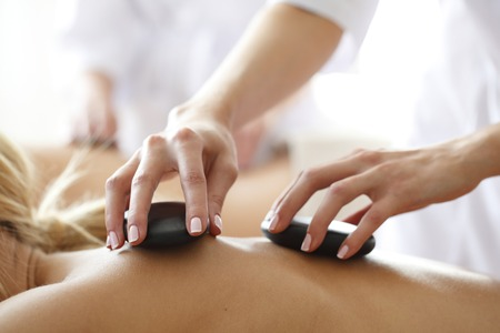 Young beautiful woman in spa getting hot stone massage 스톡 콘텐츠