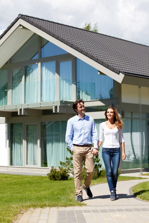 couple walking from house while holding hands