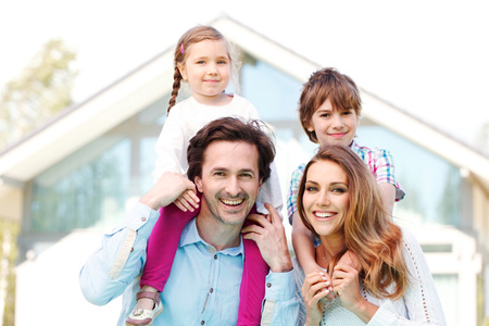 house outside: happy family standing in front of the house Stock Photo