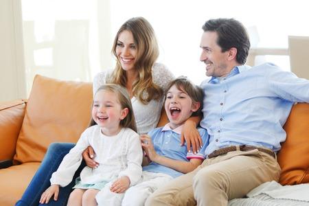 uvnitř: šťastná rodina sleduje film, zatímco sedí na gauči Reklamní fotografie