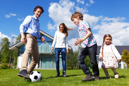 family playing football in front of their house Zdjęcie Seryjne