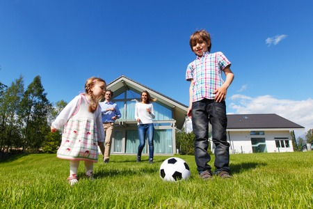 family playing football in front of their house 写真素材