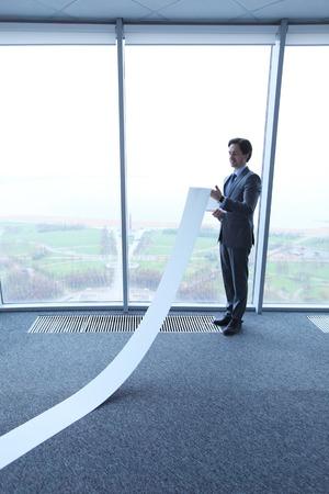 long: Office worker unrolling long sheet of paper