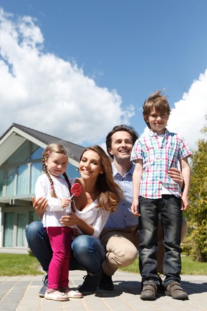 outside: happy family standing in front of the house Stock Photo