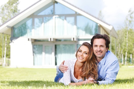 family on grass: happy couple lying in front of their house Stock Photo