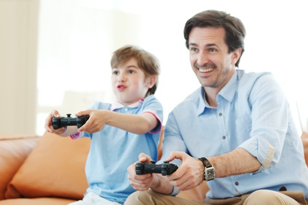 father and son play video game inside their house