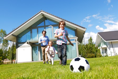 family: familie voetballen in de voorkant van hun huis