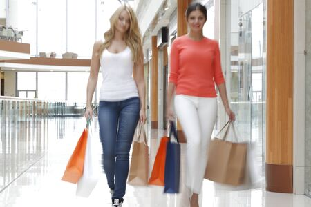 lifestyle shopping: Women walking fast in shopping mall with bags Stock Photo