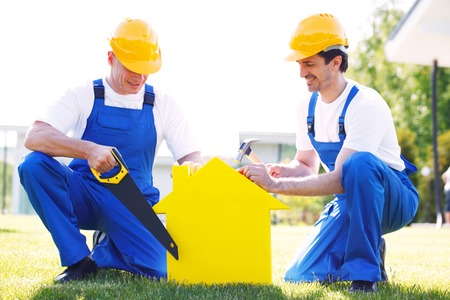 yellow house: two workmen and yellow house symbol Stock Photo