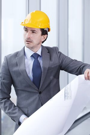 executive helmet: Architector in hardhat and business suit with construction plans Stock Photo