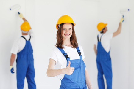young worker: workman gives thumbs up in front of two painters