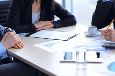 会議中に財務報告書を議論するビジネス人々 写真素材