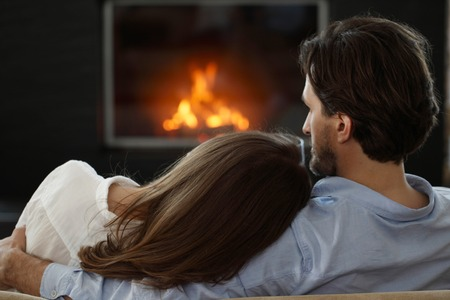 Young couple next to the fireplace Stockfoto