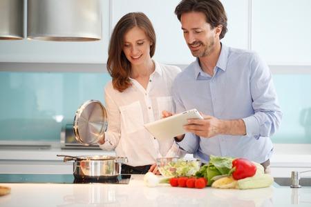 hombre cocinando: Pareja preparando la cena en la cocina