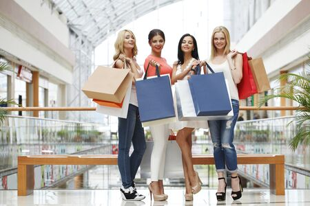 retail shopping: Happy young women with shopping bags posing in mall Stock Photo
