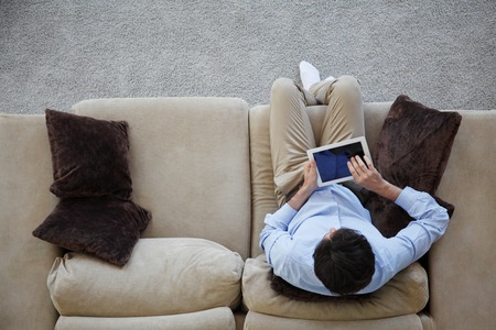 man sitting on couch with tablet from top view