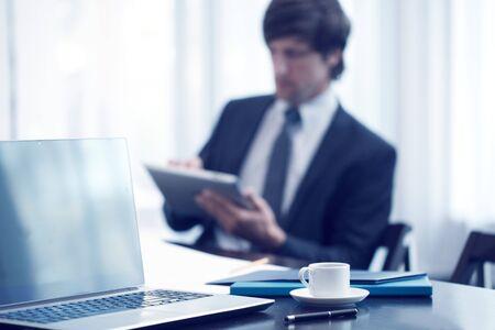 reunion de trabajo: hombre de negocios con la tableta en la reunión de trabajo Foto de archivo