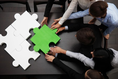 concept of business team solving puzzle Stock Photo