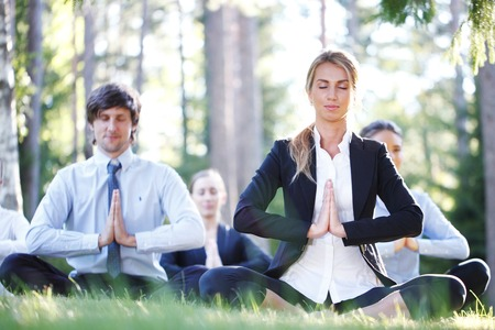 business people doing yoga at the park